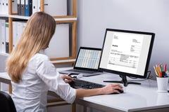 检查在计算机上的女实业家发货票 库存图片