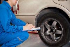 检查在车库的车胎的年轻汽车技术员 免版税库存照片