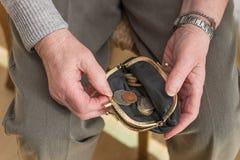 检查在钱包的领抚恤金者的手零钱 免版税图库摄影
