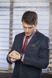 检查在他的手表的英俊的执行委员时间 库存照片