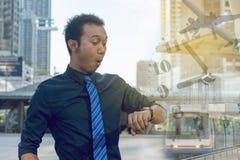 检查在他的手表的年轻商人时间 时间飞行t 库存图片
