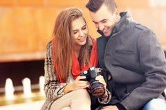 检查在他们的照相机的年轻夫妇图片 免版税图库摄影