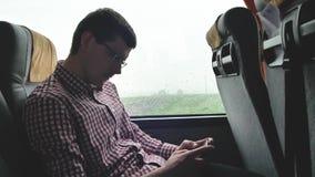 检查在他的年轻人电子邮件通勤对工作乘在一次长的旅行的公共汽车 使用一个手机特写镜头  影视素材