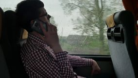 检查在他的年轻人电子邮件通勤对工作乘在一次长的旅行的公共汽车 使用一个手机特写镜头  股票录像