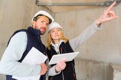 检查在建造场所的两名工作者前个细节 免版税库存图片