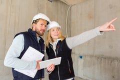 检查在建造场所的两名工作者前个细节 免版税库存照片