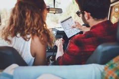 检查在roadtrip的年轻夫妇一张地图 库存照片