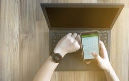 检查在smartwatch的人的关闭日程表议程同步智能手机使用在木桌上的膝上型计算机与从窗口的阳光 免版税图库摄影