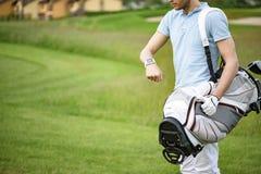检查在smartwatch的年轻高尔夫球运动员时间 免版税图库摄影