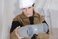 检查塑料管子的女性建造者 图库摄影