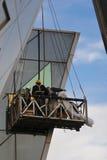 检查外壁玻璃的建筑工人 免版税图库摄影