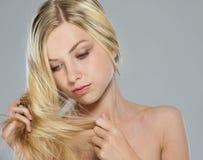 检查头发末端的白肤金发的女孩纵向 库存图片