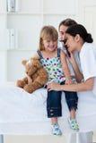 检查女孩小患者s的耳朵严重 免版税图库摄影