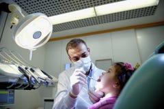 检查女孩的牙的牙医说谎在长沙发 库存图片