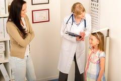 检查女孩高度评定医疗儿科医师  免版税图库摄影