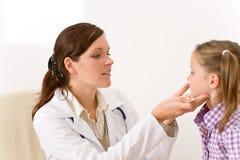 检查女性喉咙痛的儿童医生 免版税图库摄影
