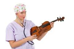 检查女性小提琴的医生 图库摄影