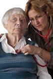 检查女性耐心的前辈的医生 免版税库存照片
