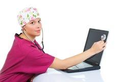 检查女性膝上型计算机听诊器的医生 免版税库存照片