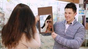 检查她在一个镜子的性感的美丽的妇女新的玻璃在光学商店,光学,眼镜师零售店,镜片 影视素材