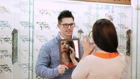 检查她在一个镜子的性感的美丽的妇女新的玻璃在光学商店,光学,眼镜师零售店,镜片 股票录像