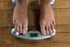 检查她的在一个称量器的妇女重量 免版税库存图片