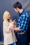 检查她的在一个英俊的人前面的性感的白肤金发的妇女电话 图库摄影