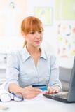 检查她的在互联网上的俏丽的妇女银行帐户从家 库存照片