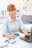 检查她的在互联网上的俏丽的妇女银行帐户从家 免版税库存照片