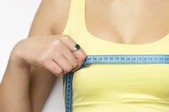 检查她的在白色背景的一名年轻适合愉快的妇女的图片乳房测量 库存图片