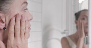 检查她的在镜子的美丽的少妇面孔 股票录像