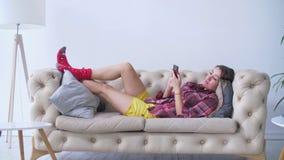 检查她的在长沙发的轻松的妇女手机 影视素材