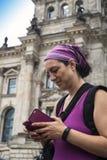 检查她的在Reichstag前面的游人智能手机 免版税库存照片