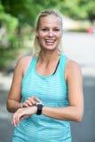 检查她的心率手表的女运动员 免版税图库摄影