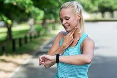 检查她的心率手表的女运动员 免版税库存照片