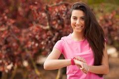 检查她的手表的体育妇女 免版税库存照片