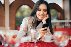 检查她的智能手机的妇女在餐馆 免版税库存照片