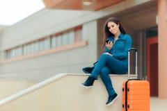 检查她的智能手机的旅行女孩,当等待在机场时 库存照片