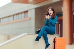 检查她的智能手机的旅行女孩,当等待在机场时 免版税库存照片