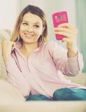 检查她的电话和采取selfies的妇女 免版税库存照片