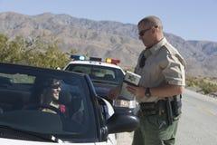 检查妇女的执照的交通官员 库存图片