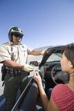 检查妇女的执照的警察 免版税库存图片