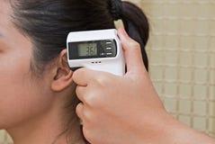 检查妇女的耳朵的医生的手与红外数字体温计 库存照片
