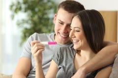 检查妊娠试验的愉快的夫妇 免版税库存图片