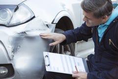 检查对汽车的损伤和填装在R的自动车间技工 免版税库存照片