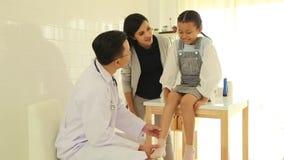 检查小女孩的年轻男性医生在办公室 股票录像