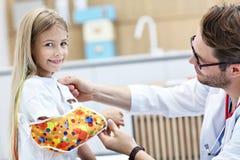 检查小女孩` s被伤的胳膊的绷带男性儿科医生 免版税图库摄影