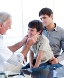 检查少许s前辈喉头的男孩医生 免版税库存图片