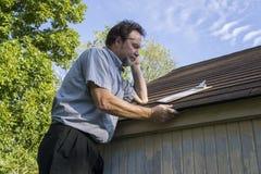 检查屋顶的保险调解人冰雹损伤 免版税库存照片