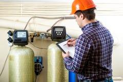 检查工业设备的工作在工厂的工作者 免版税库存照片